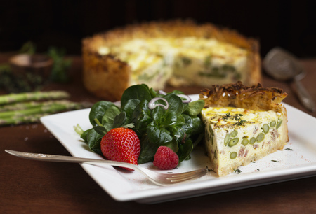 Slice of quiche with spinach and strawberry salad