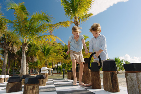 Brother and sister playing giant chess, Providenciales, Turks and Caicos Islands, Caribbean LANG_EVOIMAGES