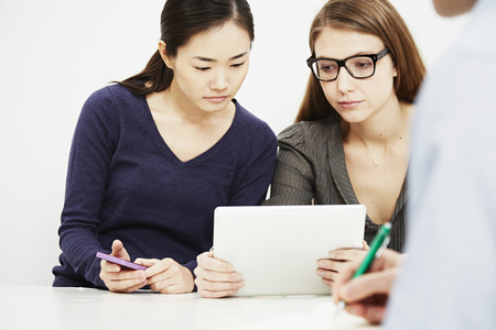 Two young women using digital tablet