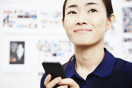 Young woman using smartphone LANG_EVOIMAGES