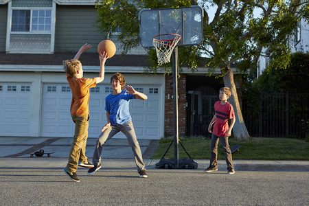Boys playing basketball outside house LANG_EVOIMAGES