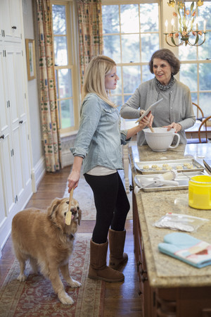 electronic organiser: Young woman treating dog whist baking with grandmother