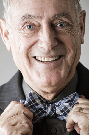 60 64 years: Senior man putting on bow tie LANG_EVOIMAGES
