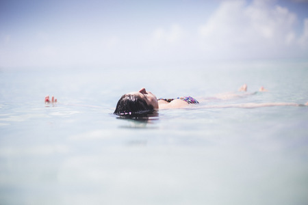 liberating: Woman floating in the sea