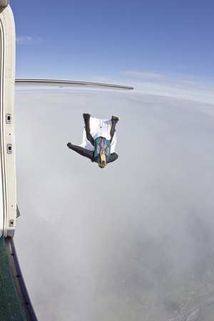 plan éloigné: Mid adult man flying above clouds in wingsuit