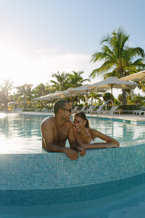 bikini top: Young couple standing in swimming pool, Providenciales, Turks and Caicos Islands, Caribbean