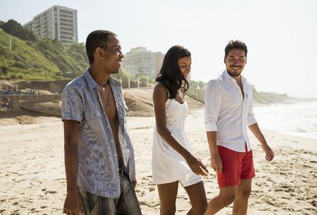 Three friends strolling on Arpoador beach, Rio De Janeiro, Brazil