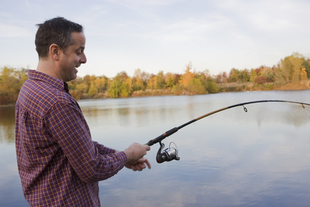 Mature male fisherman reeling in catch from lake