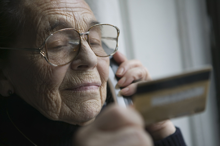 aging american: Senior woman on the phone with credit card