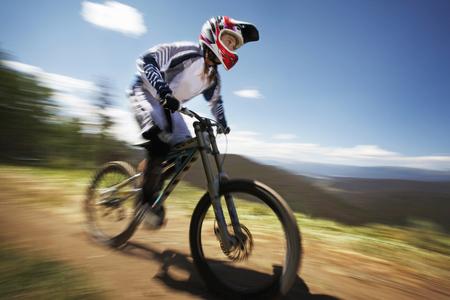 Female mountain biker speeding down dirt track LANG_EVOIMAGES