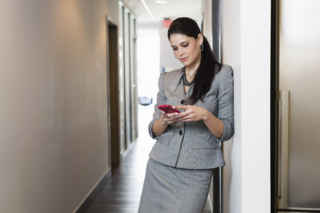 passageways: Young businesswoman using smartphone LANG_EVOIMAGES