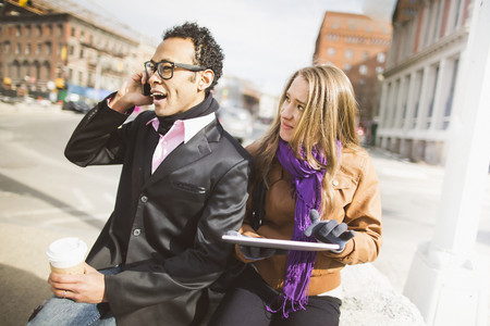 Young couple with cellphone and digital tablet in New York, USA LANG_EVOIMAGES