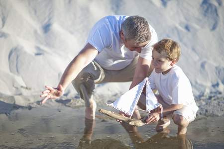 Father and son playing toy boat on beach LANG_EVOIMAGES