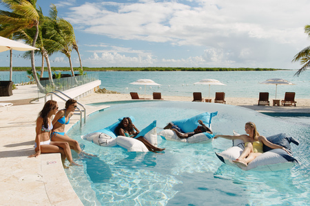 Group of young adults relaxing in swimming pool, Providenciales, Turks and Caicos Islands, Caribbean LANG_EVOIMAGES