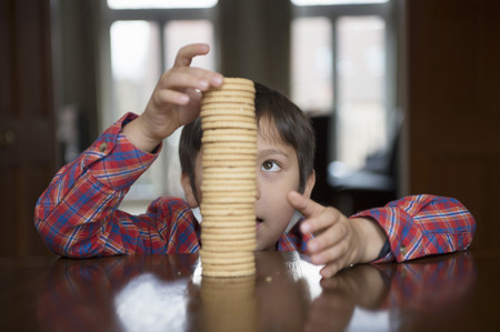 Boy stacking up biscuits