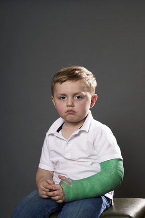 Portrait of sullen young boy with plaster cast on arm LANG_EVOIMAGES