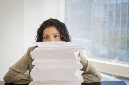 concealing: Portrait of businesswoman with a stack of paperwork