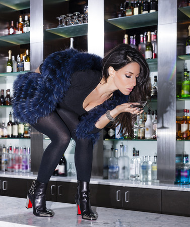 jesting: Mid adult woman in cocktail bar bending forward holding drink LANG_EVOIMAGES