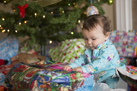 Baby girl opening presents on her first Christmas LANG_EVOIMAGES
