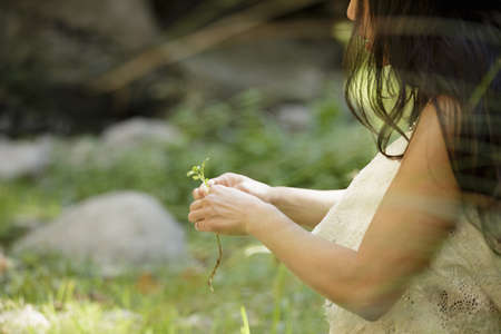 Mid adult woman holding foliage LANG_EVOIMAGES