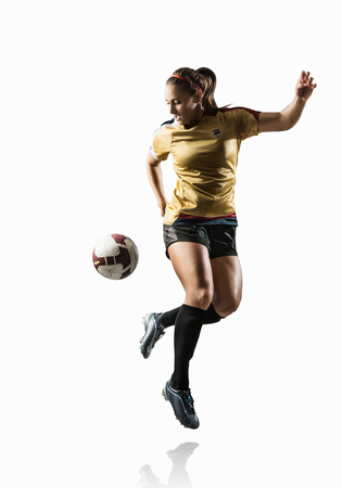 athleticism: Studio shot of young female soccer player back kicking ball