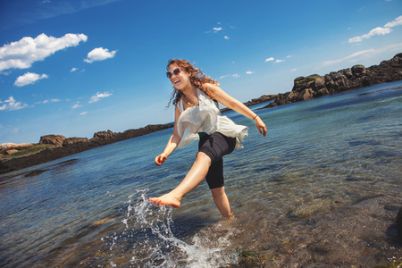 kick around: Young woman in the sea at the rocky coastal beach in Biddeford, Maine, USA LANG_EVOIMAGES