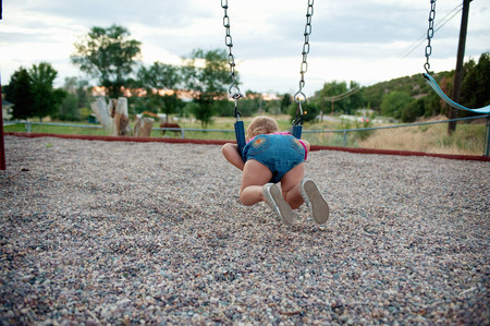 fedup: Rear view of female toddler lying on park swing