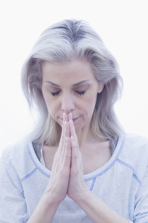 bowing head: Mature woman in prayer pose
