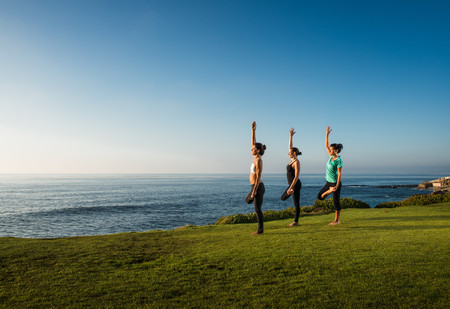 getting out: Women on cliff, in yoga positions LANG_EVOIMAGES