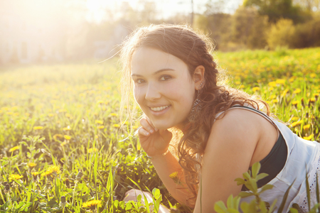 Young woman lying in field LANG_EVOIMAGES