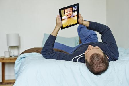 pyjama: Mid adult man lying on bed holding up digital tablet