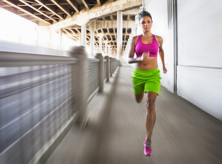 athleticism: Blurred shot of young woman running on urban bridge LANG_EVOIMAGES