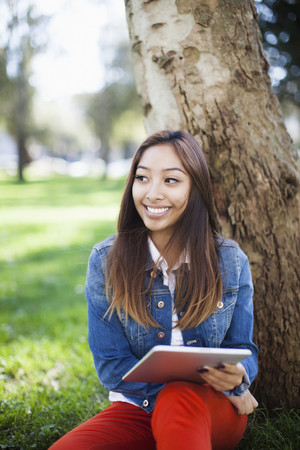 Young woman leaning against tree, using digital tablet