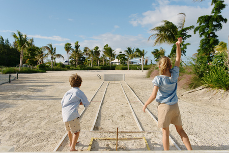Brother and sister playing horseshoe game, Providenciales, Turks and Caicos Islands, Caribbean