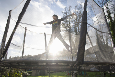 energy work: Boy jumping on outdoor trampoline