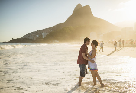 each year: Young couple hugging at sunset, Ipanema Beach, Rio, Brazil