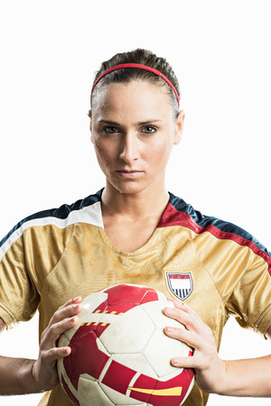 athleticism: Studio portrait of young female soccer player holding ball LANG_EVOIMAGES