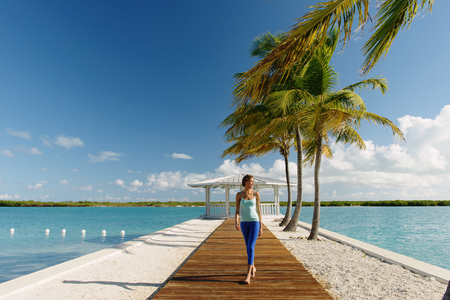 territory: Young woman strolling on pier, Providenciales, Turks and Caicos Islands, Caribbean