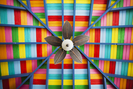 chillout: Petal-shaped fan on multi-coloured wooden ceiling