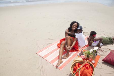 tweens: Mother and children relaxing on beach