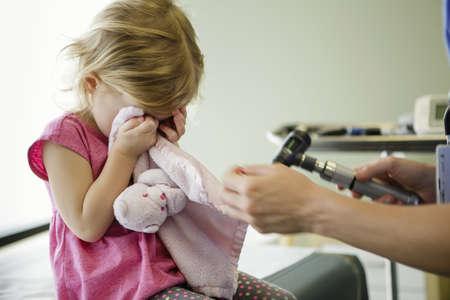 Girl hiding eyes in hospital room