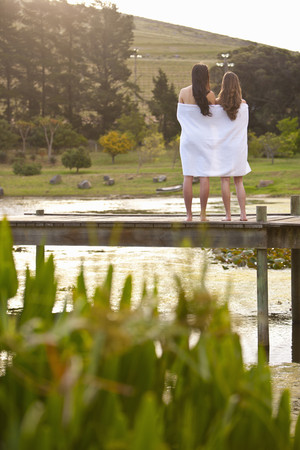 Two young women standing on river pier wrapped in blanket
