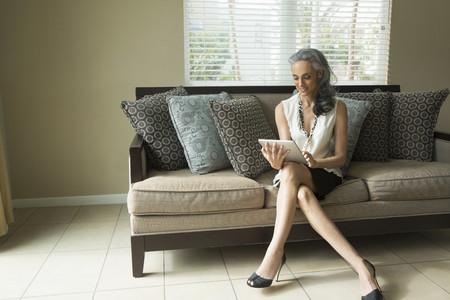 tallness: Woman using digital tablet on sofa