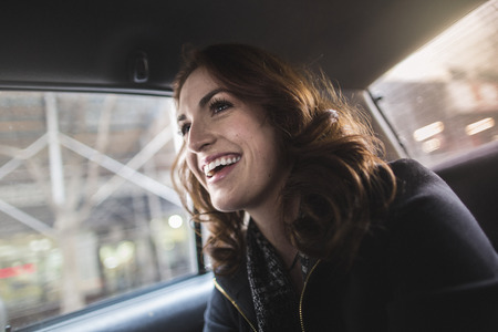 taxicabs: Happy young woman in back seat of taxi LANG_EVOIMAGES