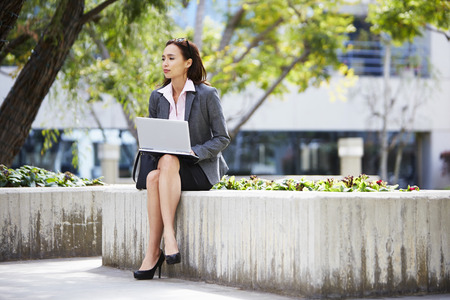 Young female businesswoman using laptop outside office