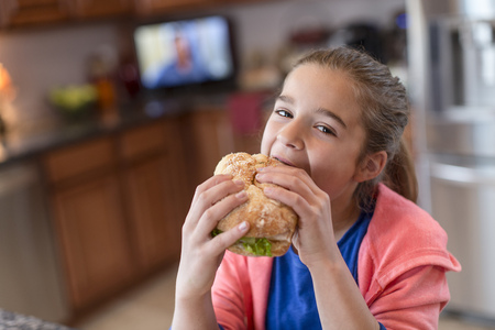 Girl in kitchen biting sandwich