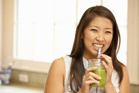 Young woman sipping green smoothie LANG_EVOIMAGES