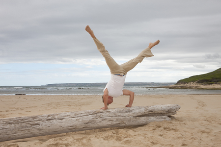 Young man doing handstand on tree trunk at beach LANG_EVOIMAGES