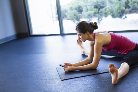 Young woman in yoga posture using cellular phone