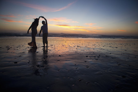 mirroring: Couple dancing on beach at sunset, Cape Town, South Africa